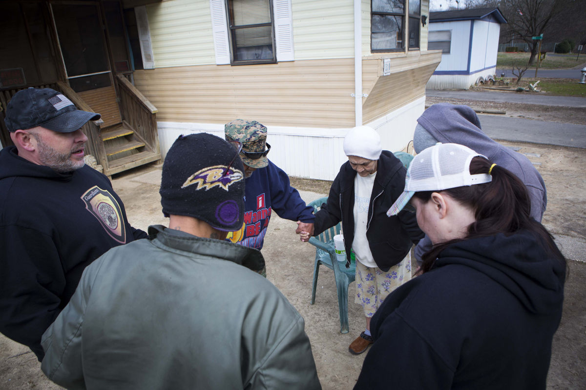 "Chris Lane (left) with the Guardians community organization prays with Geraldine Mondido, 67 (center right), and her family outside their mobile home in Harbour East Village on West Hundred Road. ""There is so much despair, which just means 'without hope.' You have to give people a purpose,"" he says."