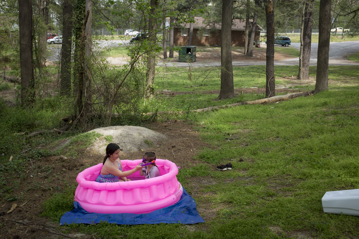 "Angelina (left) sits in a pool with a friend behind her home along Jefferson Davis Highway in Chesterfield County. Angelina and her mother, Angie Smith, used to live at Americas Best Value Inn but now live in a rental cabin. Despite having bed bugs at one point and other problems in her new home, Smith says it is much better than the motel. ""People may say it's bad here, too, but I love having these woods behind our house for the kids to play in,"" she said."
