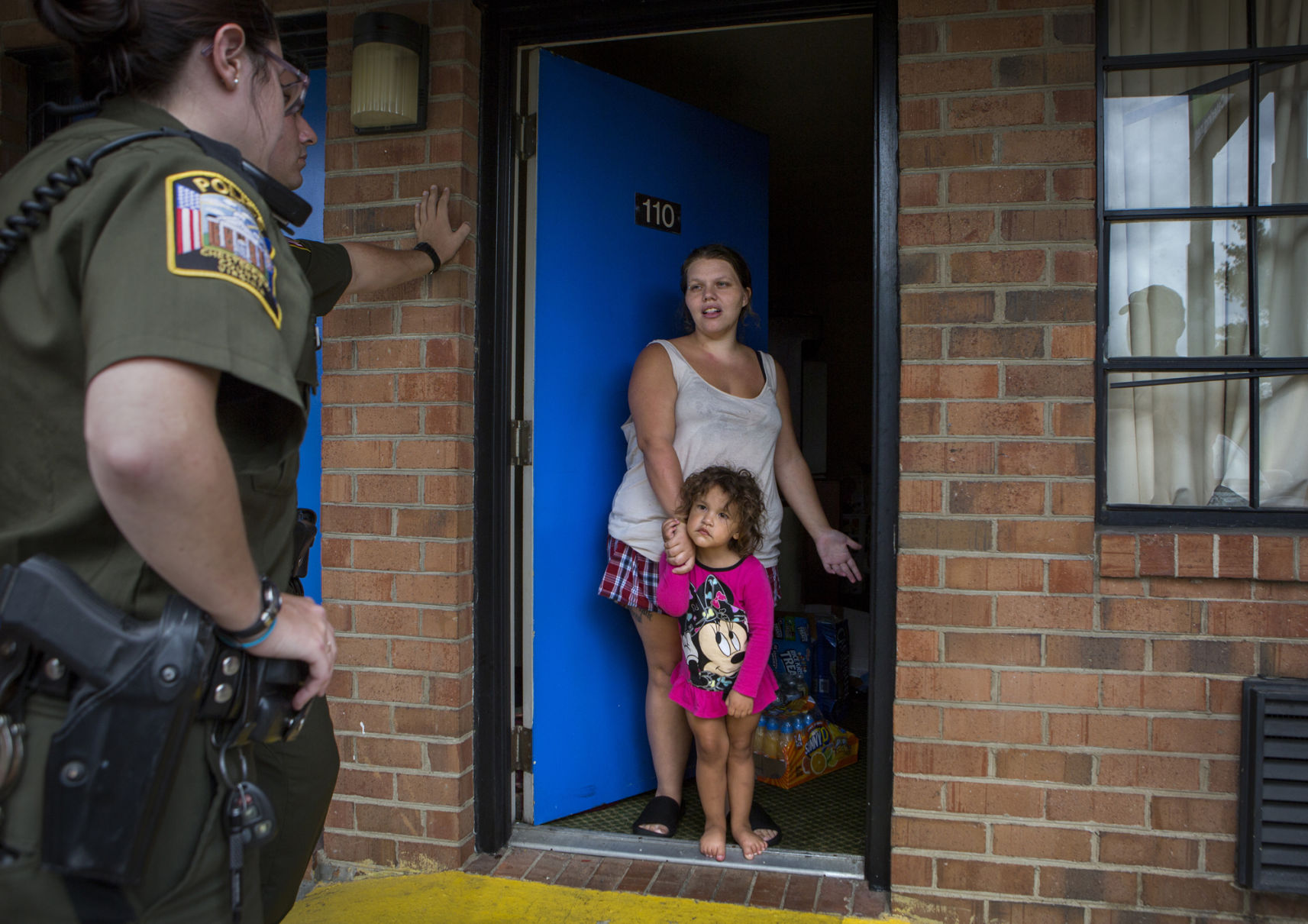Kelsey Ratliff stands with her daughter Liliana, 2, in the doorway of their room at Americas Best Value Inn while Chesterfield County police officers explain that she must vacate the property. Ratliff had lived at the motel since Christmas 2016, but because she has switched rooms, the Landlord-Tenant Act does not apply to her and she is not eligible for the official eviction process.