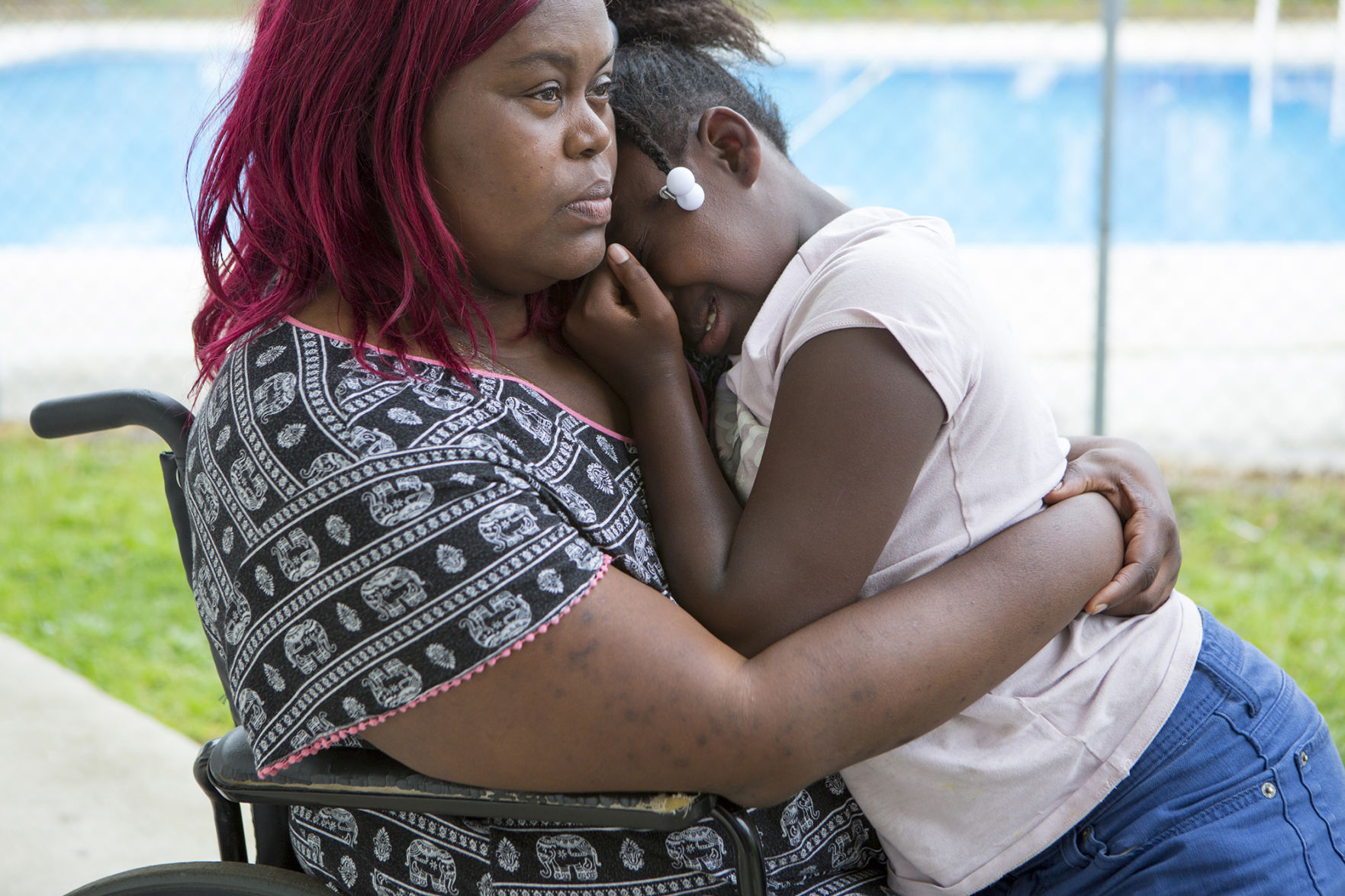 "Latisha Ragland holds her daughter Annarenee, then 9, as she cries about her hunger pangs in May outside the motel room in Petersburg, where they have lived for several months. Ragland, who uses a wheelchair after a leg amputation, receives $735 in disability benefits each month, but her room at the motel costs $220 a week. ""When it gets time for the rent to be due and I can't pay, I feel my chest caving in,"" she said."