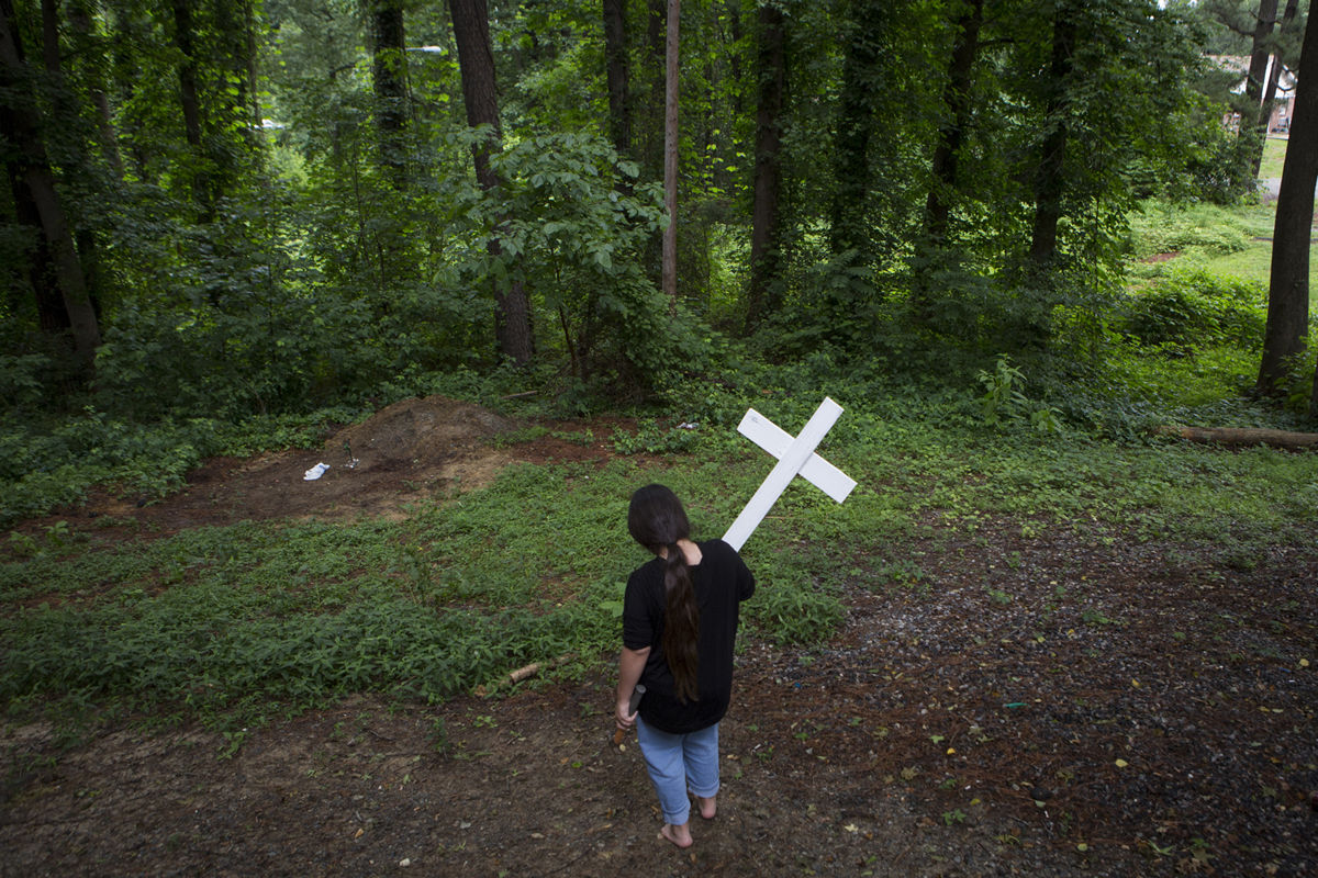 Angie Smith's daughter Angelina carries a homemade cross behind her home along Jefferson Davis Highway to mark her dog's grave. The dog died two days after Smith's partner, Kameel Mohammed, died.